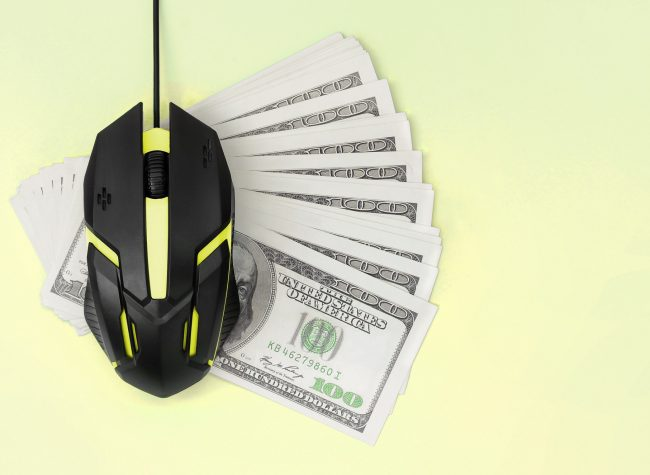 Computer mouse on many dollar bills
